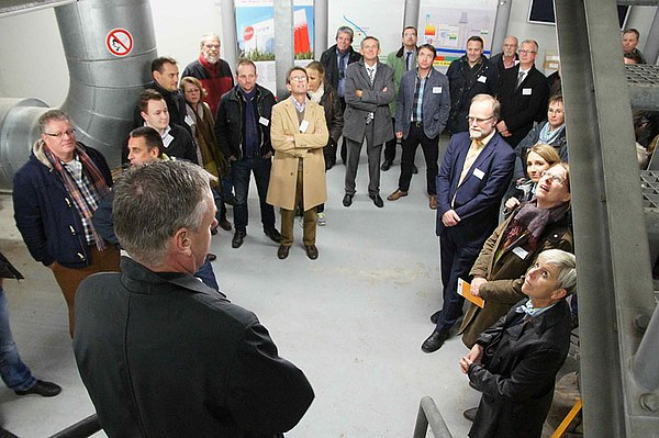 Geschäftsführung, Bürgermeister und Gäste lauschen dem Vortrag des Experten.