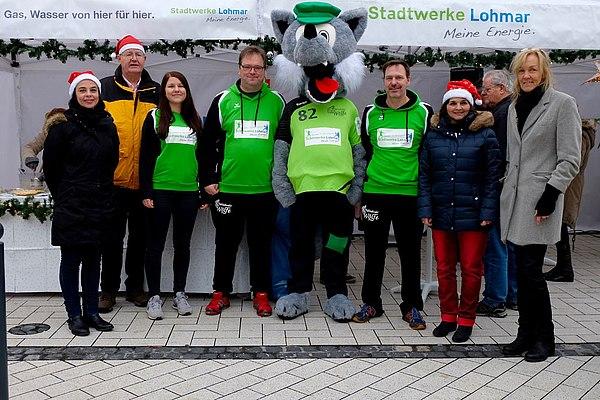 Der Wolf und die 7 Geißlein, Abteilungsleiter Handball und Mitarbeiter der Stadtwerke Lohmar mit dem Wolf vor dem Weihnachtsstand (Foto: Markus Goertz)